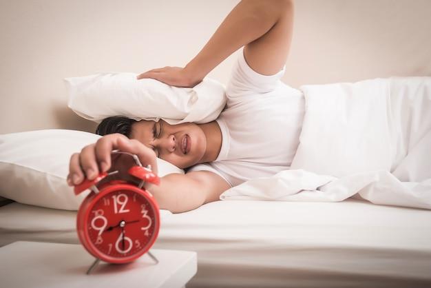 Man hand turns off the alarm clock waking up at morning Free Photo