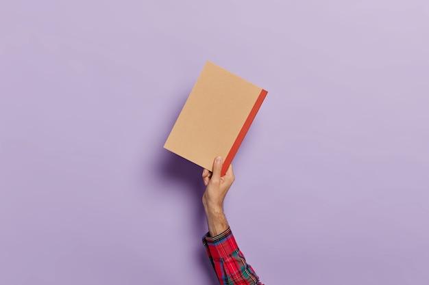 Рука человека с пустым дневником, изолированным над фиолетовым Бесплатные Фотографии