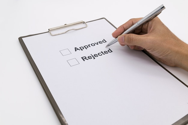 Man hand with pen over document, select approved or rejected. Premium Photo
