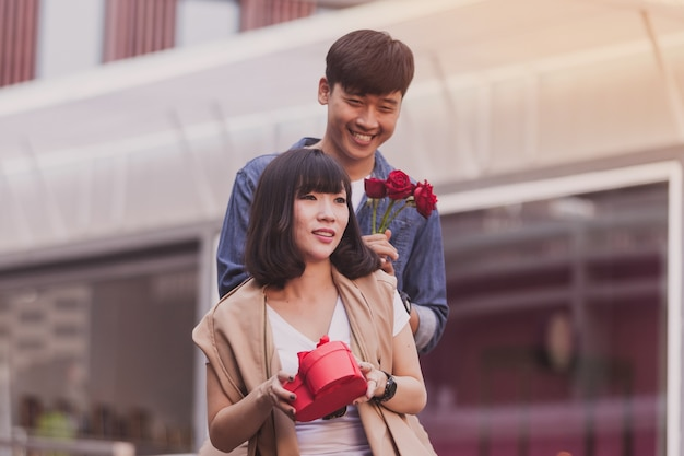 Man handing a gift and roses to a woman Free Photo