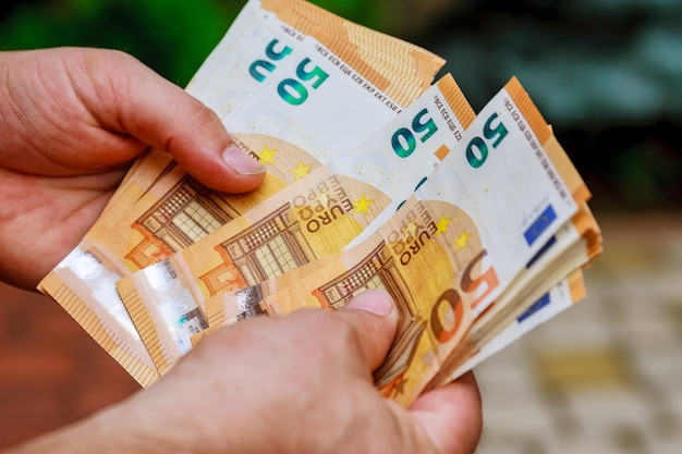 Человек руки считает банкноты евро нас. считать или потратить деньги. Premium Фотографии