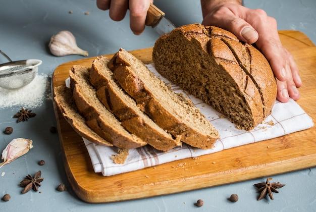 男の手がライ麦パンのナイフの作品でカット 無料写真