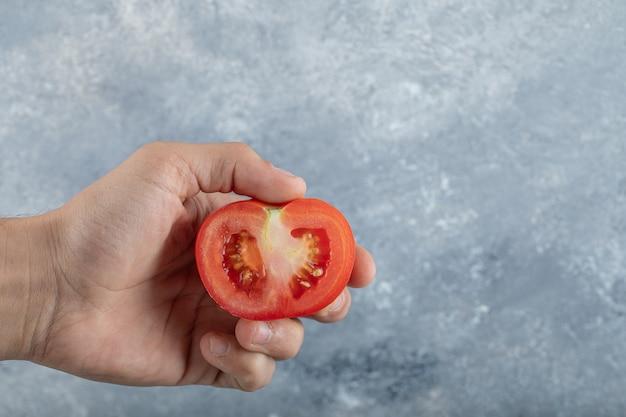 赤いトマトのスライスを保持している男の手。高品質の写真 無料写真
