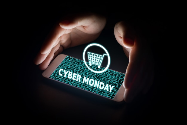Man hands holding smart phone with cyber monday text and cart on virtual screens on smartphone. Premium Photo