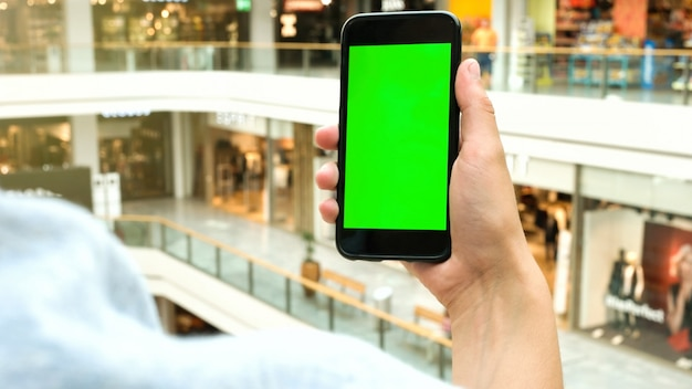 Человек руки, держа смартфон с зеленым экраном. Premium Фотографии