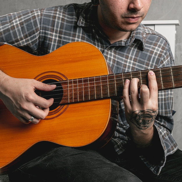 Man hands playing acoustic guitar Free Photo
