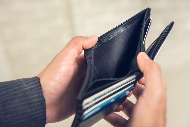 Man hands showing empty wallet with no money Premium Photo