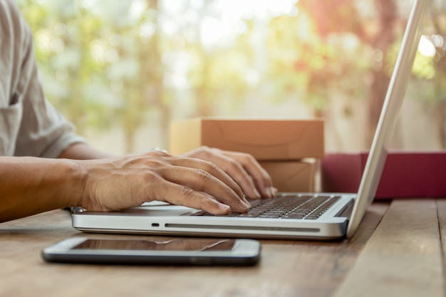 Man hands typing on laptop keyboard with parcel package delivery on table. Premium Photo