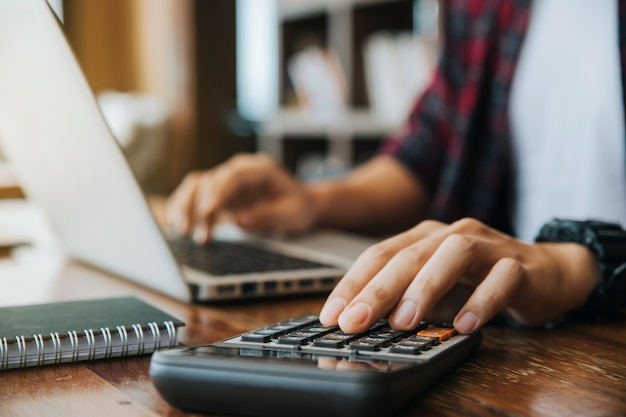 Man hands using a calculator and laptop computer for calculating with finance paper Premium Photo
