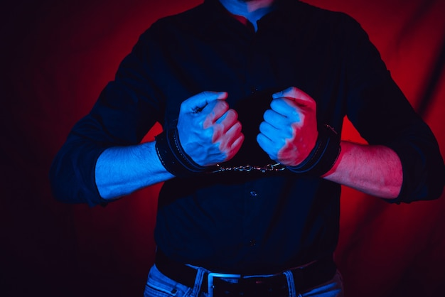 A man hands wearing a pair of black leather handcuffs Premium Photo