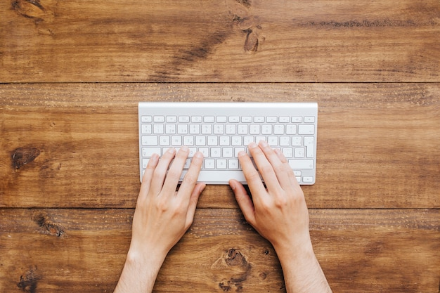 Man hands working on keyboard over wooden background Free Photo