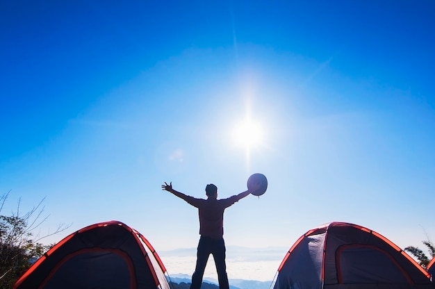 Man happy camping stand and raise his hand holding his hat on the mountain in the morning Free Photo