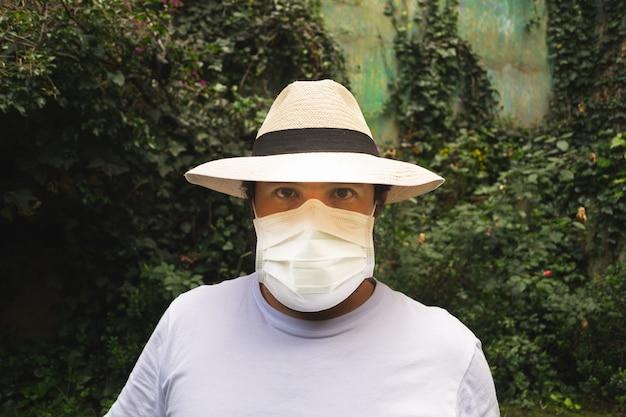 Uomo con un cappello che indossa una maschera bianca per proteggersi dalla polvere e dal coronavirus Foto Gratuite