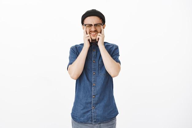 Uomo con cattiva vista che tocca gli occhi e strizza gli occhi con gli occhiali che fa smorfie durante il test dell'occhio nel negozio di ottica in piedi intenso e concentrato avendo bisogno di indossare occhiali prescritti Foto Gratuite