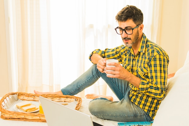 Man having breakfast on bed looking at laptop in the bedroom Free Photo