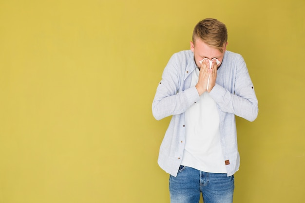 Man having cold and sneezing Free Photo