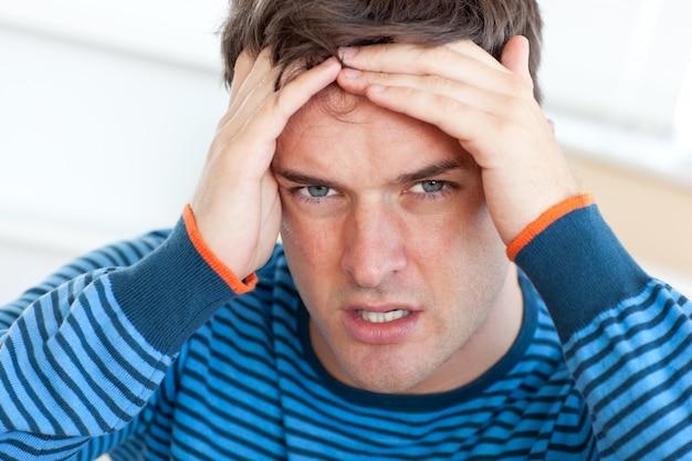 Man having a headache in the livingroom Premium Photo