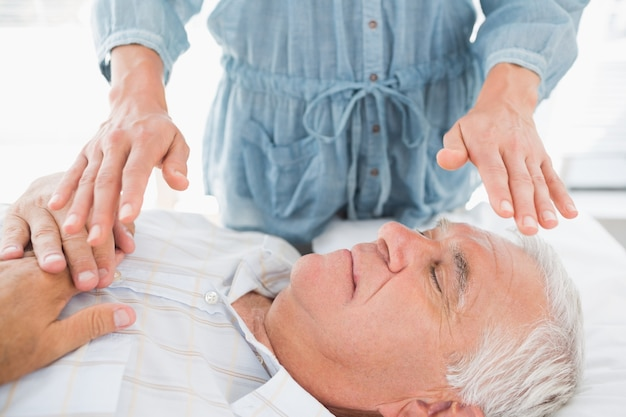 Homem tendo tratamento de reiki pelo terapeuta Foto Premium