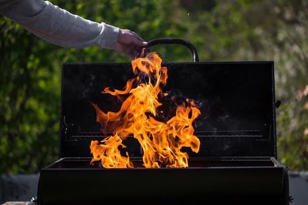 Мужчина нагревает гриль-барбекю, готовит для жарки некоторые виды мяса Premium Фотографии