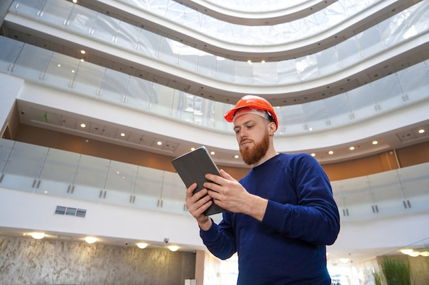 A man in a helmet in a large space with a tablet Premium Photo