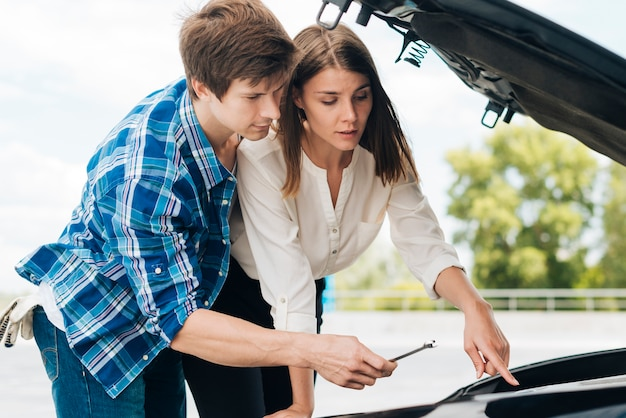 Man helping woman fix her car Free Photo