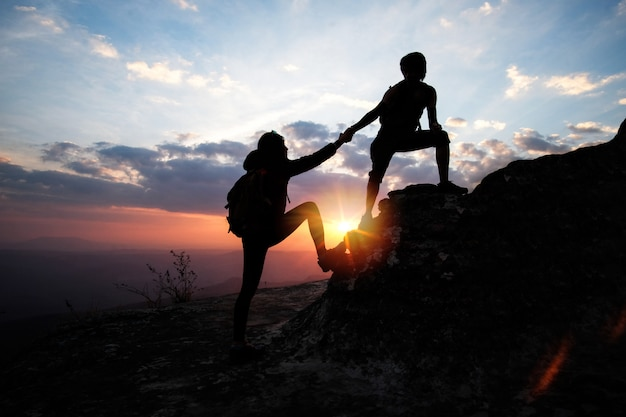 Man helping a woman to up on the mountain in hiking activity ...