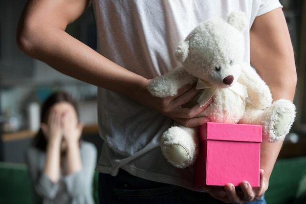 Man hiding gift making romantic surprise for wife, rear closeup Free Photo