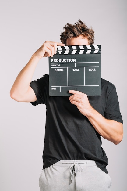 Man hiding his face behind clapperboard Free Photo