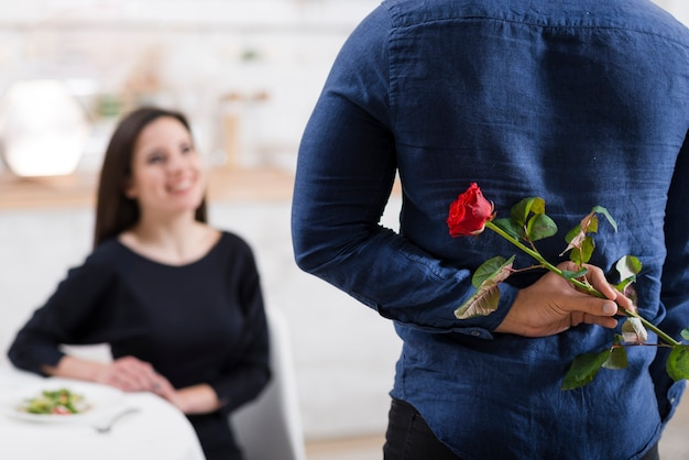 Man hiding a rose from his girlfriend Free Photo