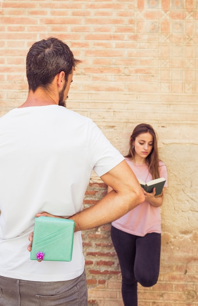 Man hiding surprise gift from her girlfriend reading book Free Photo
