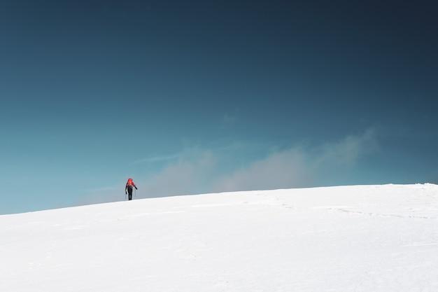 雪に覆われた山でのハイキングの男 無料写真