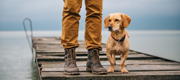 Man and his dog standing on dock Premium Photo