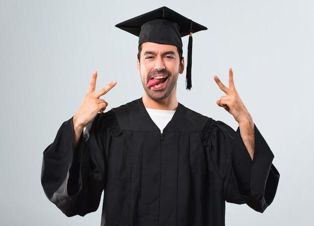 Man on his graduation day university showing tongue at the camera having funny look Premium Photo