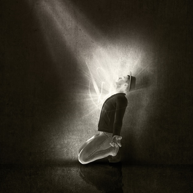Man on his knees with a ray of light Free Photo