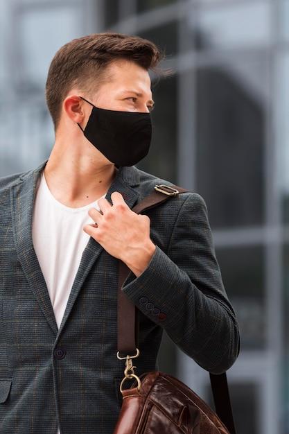 Uomo che si reca al lavoro durante una pandemia che indossa la maschera Foto Gratuite