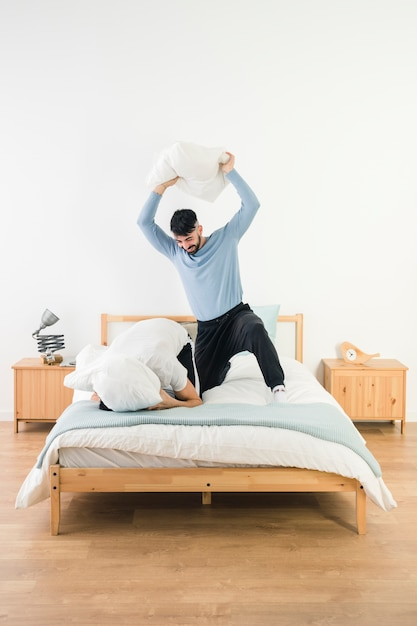 Man hitting his boyfriend with white pillow on bed Free Photo