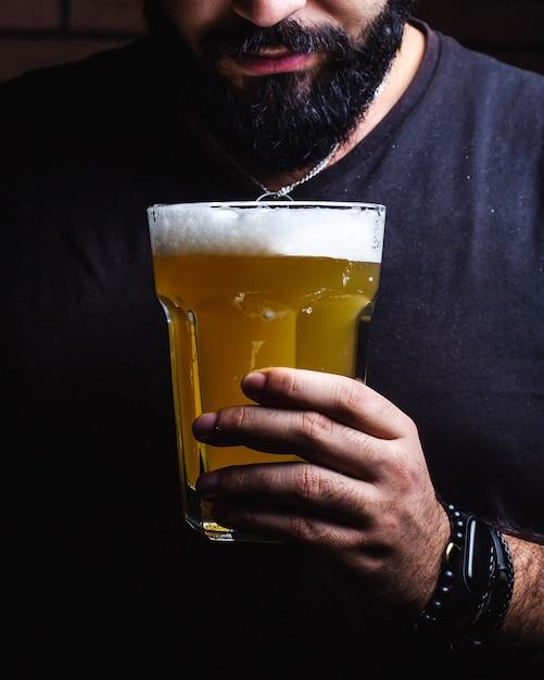 L'uomo in possesso di un bicchiere di birra Foto Gratuite