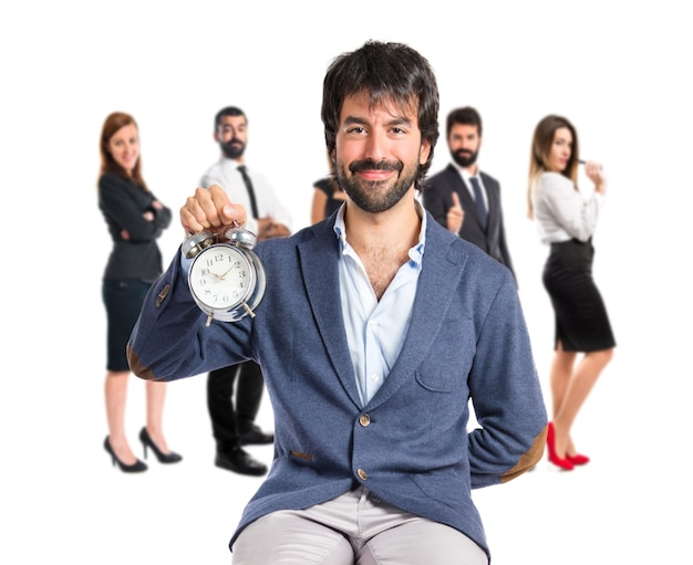 Man holding a clock over white background Free Photo