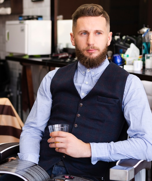 Мужчина держит стакан виски в парикмахерской Бесплатные Фотографии