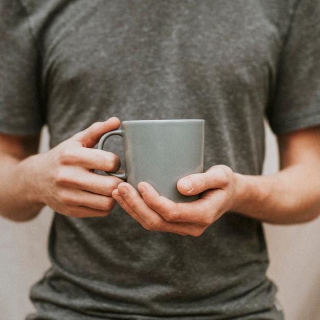 회색 세라믹 커피 잔을 들고 남자 무료 사진