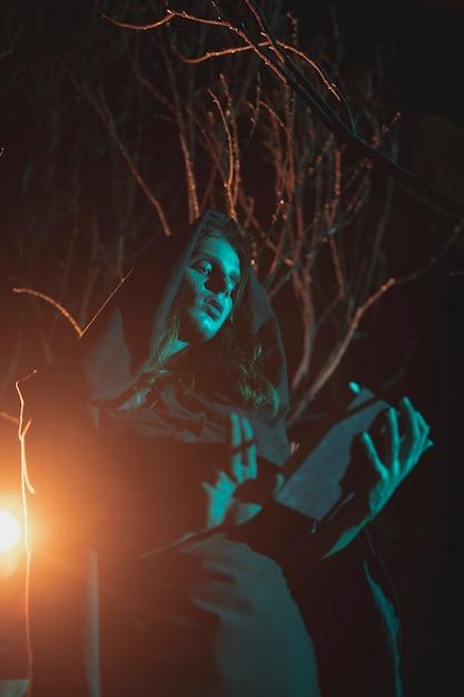 Мужчина держит фонарь и книгу в ночи Бесплатные Фотографии