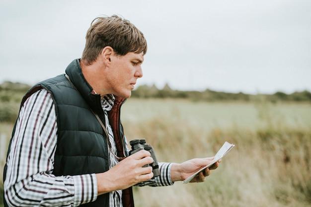 Мужчина держит бинокль Premium Фотографии