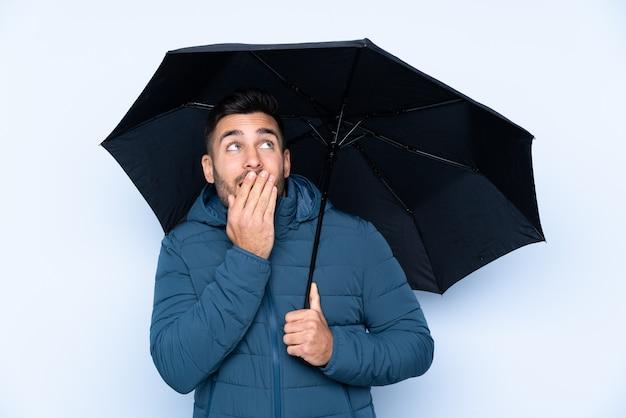 Мужчина держит зонтик над изолированной стеной с удивлением и шокирован выражением лица Premium Фотографии
