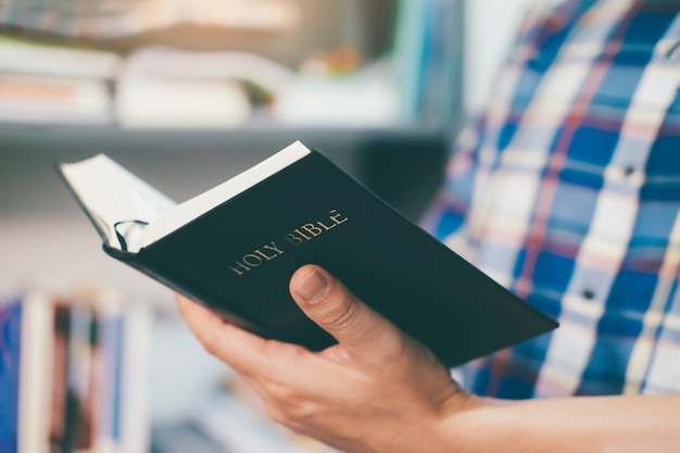 거룩한 기독교 성경을 들고 읽는 남자 프리미엄 사진