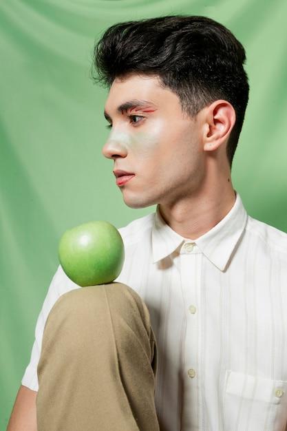 Man holding apple on knee Free Photo