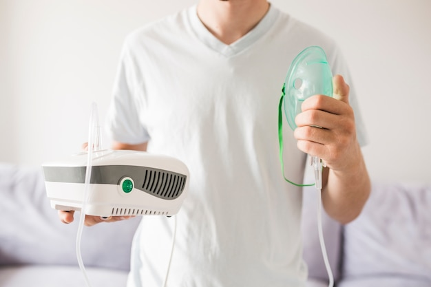 Man holding asthma nebulizer in hands Free Photo