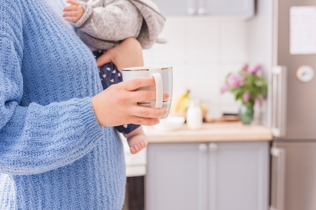 Man holding baby and mug in kitchen Free Photo
