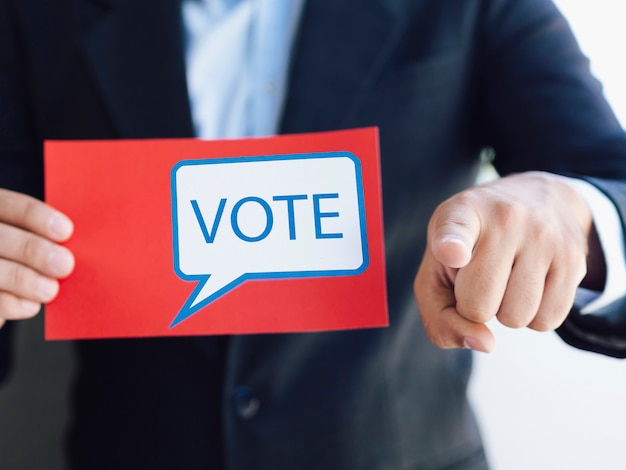 Man holding a ballot and pointing to the camera Free Photo