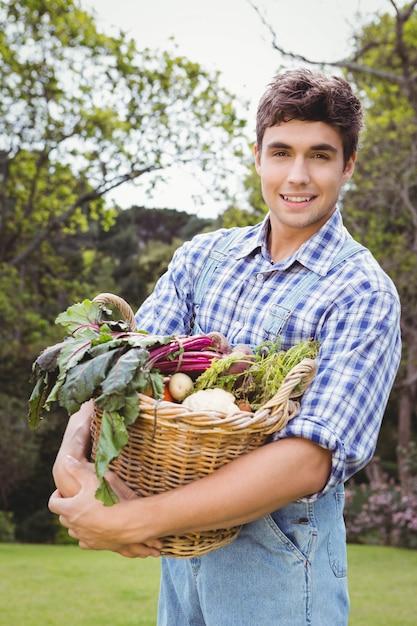Man holding a basket of freshly harvested vegetables in garden Premium Photo