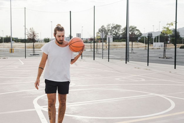 Man holding basketball in outdoor court Free Photo